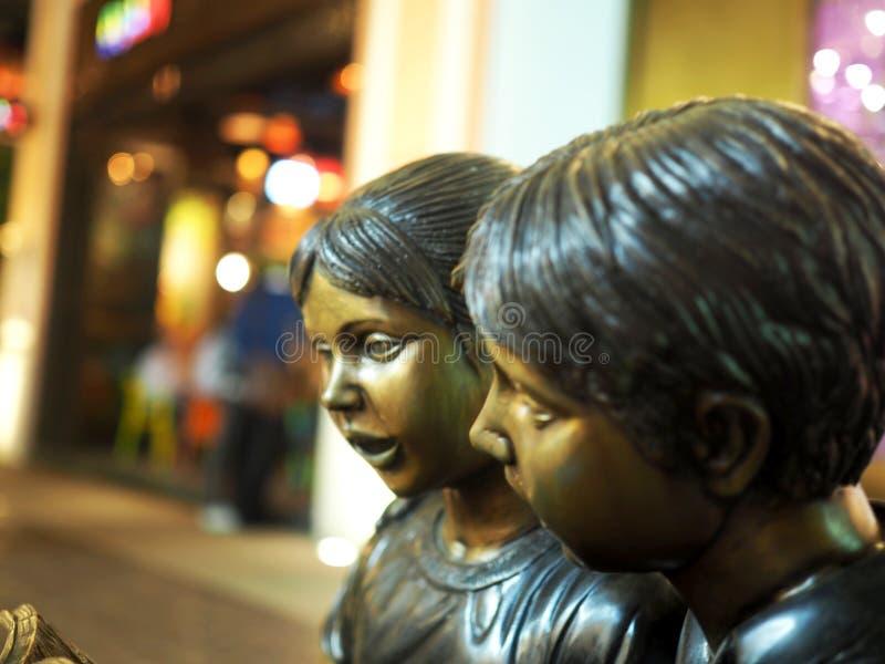 Mässingsstaty av Little Boy och flickan arkivfoto