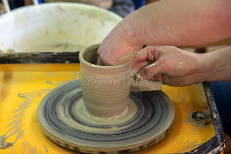 Mästarklass på framställning av en keramisk kruka med keramikers hjul Krukmakerit roterar runt om dess axel royaltyfria foton
