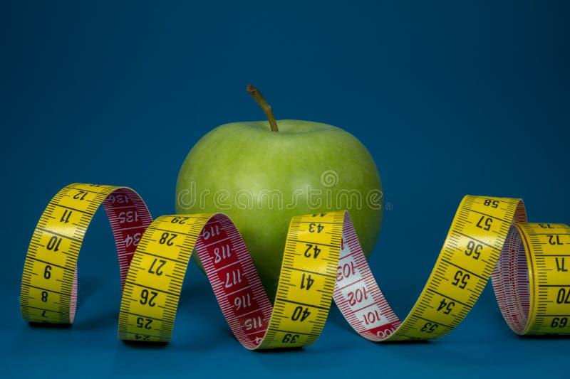 Mäta bandet och det gröna äpplet på blå bakgrund royaltyfri fotografi