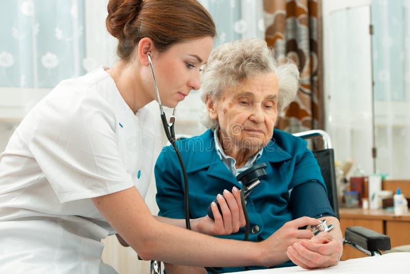 Mäta blodtryck av den höga kvinnan arkivbild