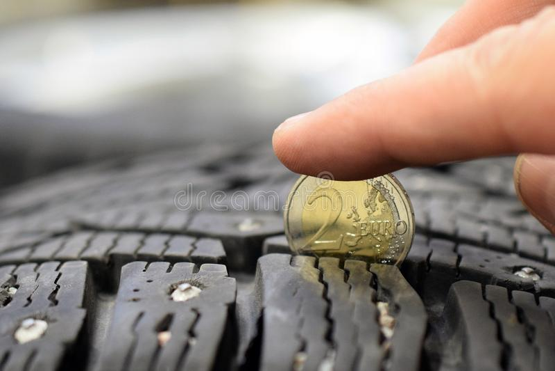 Mäta gummihjuldäckmönsterdjup med myntet royaltyfri bild