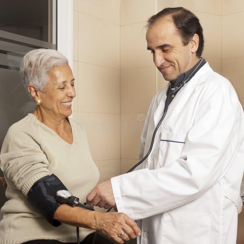 Mätande blodtryck för doktor royaltyfri foto