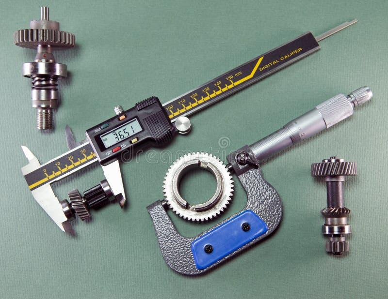 Mätning av detaljerna vid en digital klämma och en mekanisk mikrometer fotografering för bildbyråer