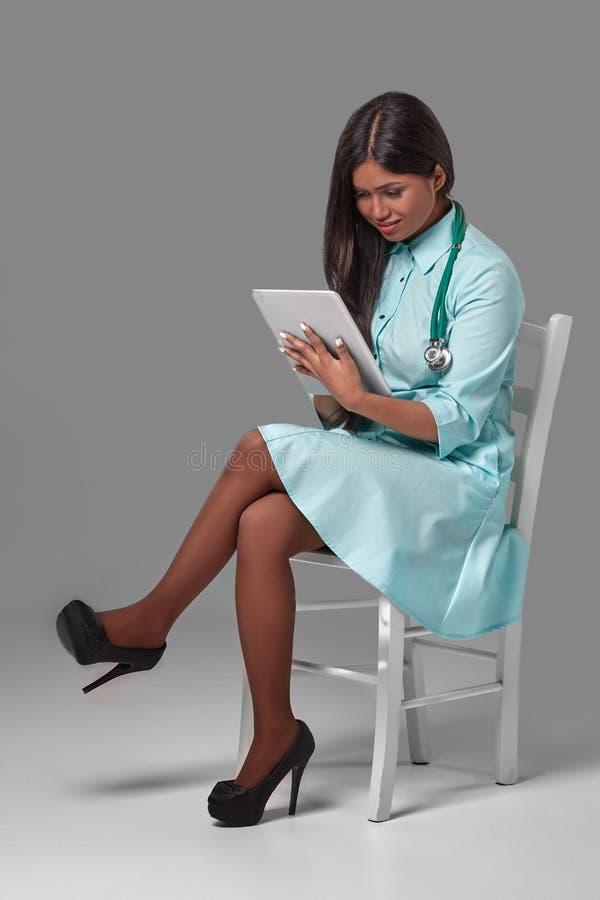 Młoda ładna lekarka z stetoskopu obsiadaniem na krześle zdjęcie stock