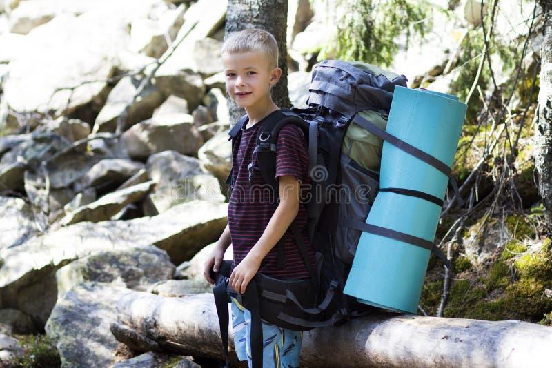 Młoda śliczna szczęśliwa dziecko chłopiec z dużym turystycznym plecakiem na pogodnym skały tle Turystyka, wycieczkować i aktywny  zdjęcia stock