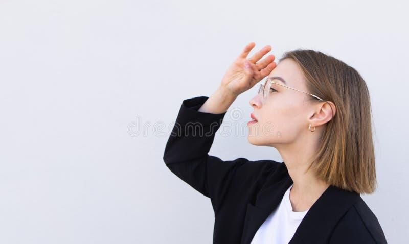Młoda atrakcyjna biznesowa kobieta w szkłach i czarnej kurtce patrzeje z ukosa na białym tle zdjęcia stock