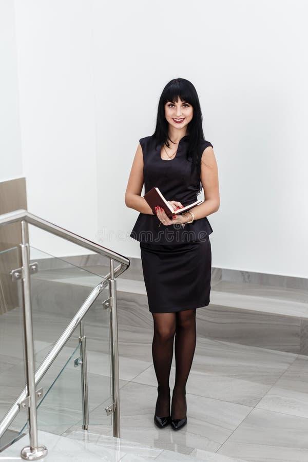 Młoda Atrakcyjna szczęśliwa brunetki kobieta ubierał w czarnym garniturze pracuje z notatnikiem, stojący w biurze, ono uśmiecha s fotografia royalty free