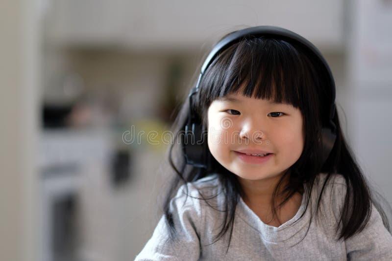 Młoda azjatykcia dziewczyna cieszy się słuchać muzyka na jej hełmofonie obraz royalty free