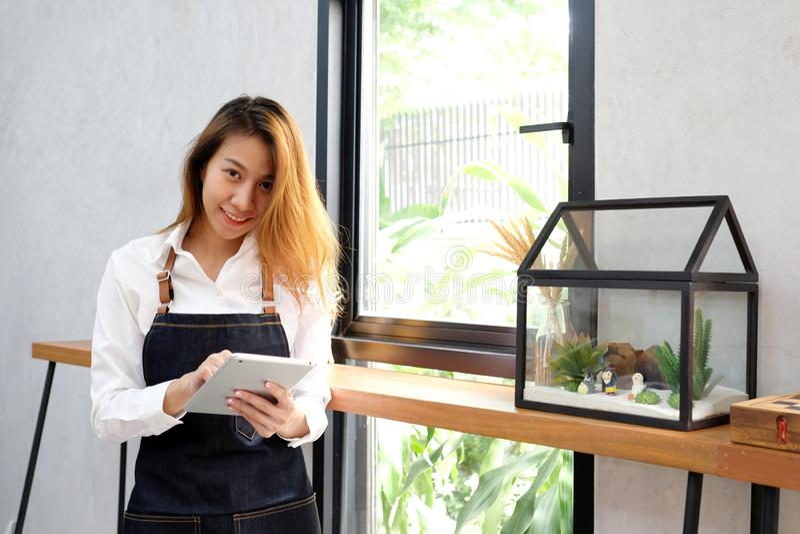 Młoda azjatykcia kobieta, barista, używać pastylkę, jedzenie i napoju pojęcie dostawać kawowego rozkaz przy kawiarnia kontuaru tł zdjęcie royalty free