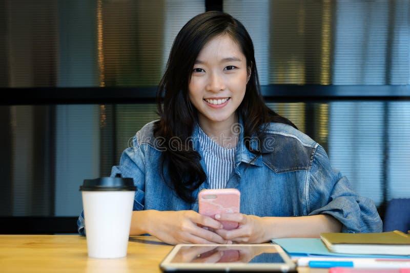 Młoda azjatykcia kobieta używa mądrze telefon przy jej biurowym biurkiem podczas gdy pracujący, pracuje w domu, przypadkowy biuro fotografia stock