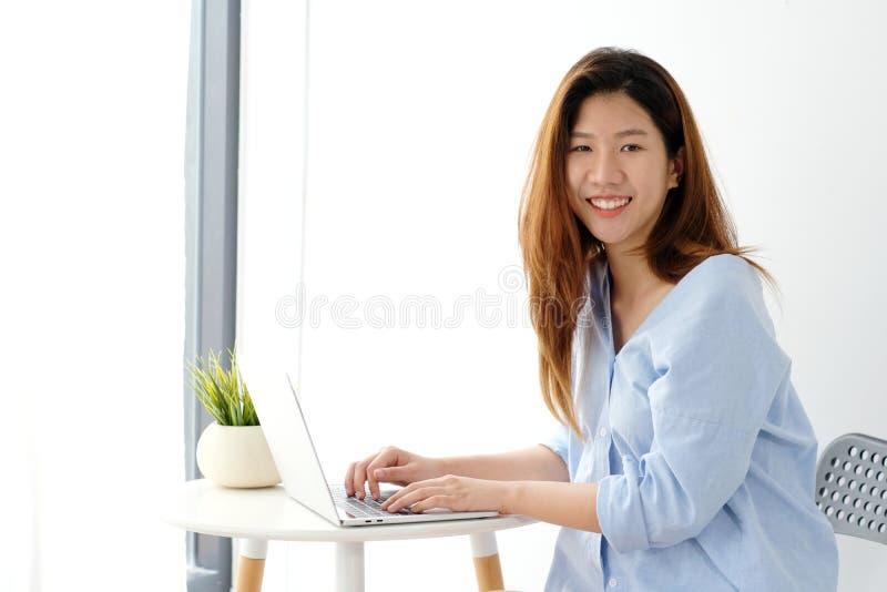 Młoda azjatykcia kobieta w przypadkowym stylu używać laptopu biurowego tło, ludzi i technologię pracuje w domu w domu, obraz royalty free