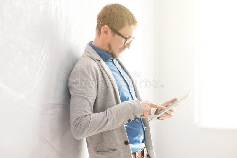 Młoda biznesmen pozycja w biurze blisko używać pastylka peceta, okno i ściany i obraz stock
