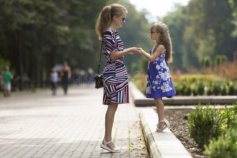 Młoda blond kobieta i mała dziecko dziewczyna w modnych sukniach trzyma ręki na pogodnej parkowej alei zdjęcie stock