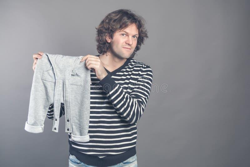 Młoda caucasian męska blaga o nowym eleganckim dziecku odziewa dla jego syna mienia w rękach i demonstrować popielatych spodnia obraz stock