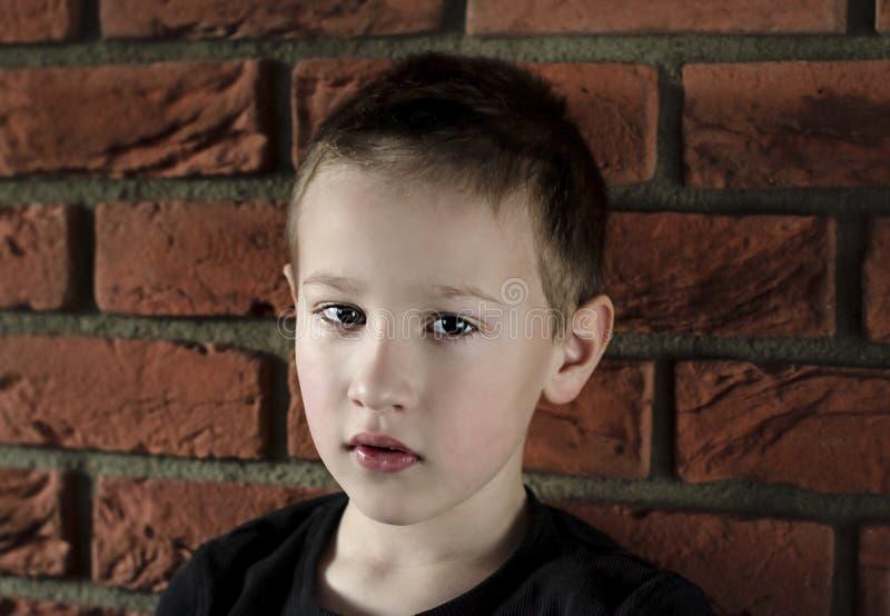 Młoda chłopiec patrzeje kamerę w czarnej koszulce W górę portreta na ślicznych boy's stawia czoło pozycję przed czerwonej cegły fotografia royalty free