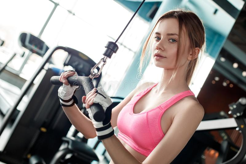 Młoda dziewczyna ćwiczy na kablowego maszynowego mienie baru przyglądającej kamerze ufnej w sport rękawiczkach w gym zdrowym styl obrazy royalty free