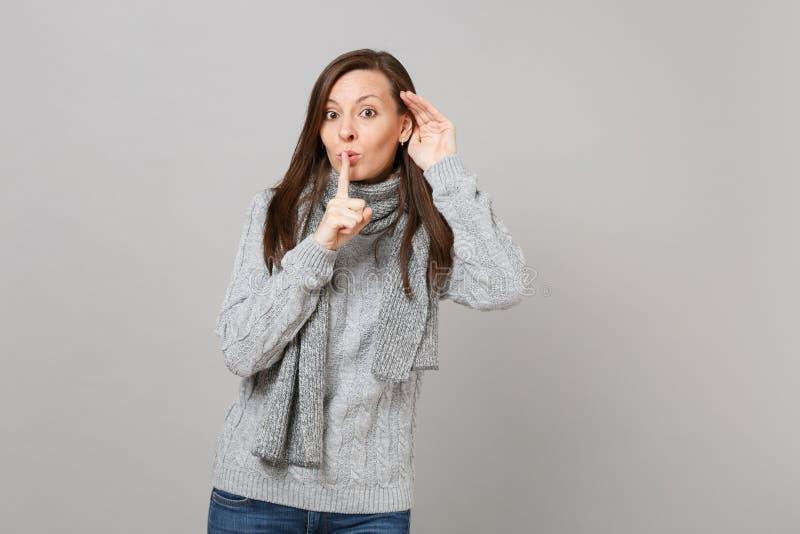 Młoda dziewczyna mówi ucichnięcie w szarym puloweru szaliku był spokojna z palcem na warga gescie shhh podsłuchuje i słuchający d fotografia stock