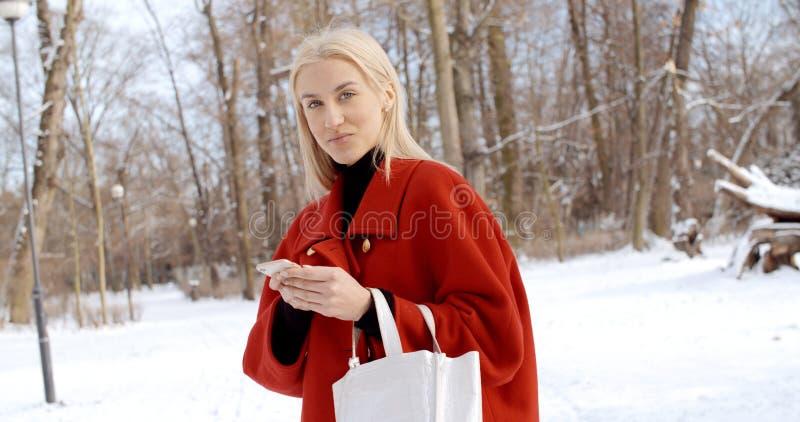 Młoda dziewczyna w czerwonym zima żakiecie używać telefon komórkowego w miasto parku fotografia stock