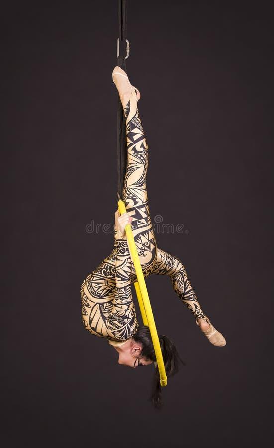 Młoda dziewczyna w kostiumu z drukiem wykonuje akrobatycznych elementy w wietrzy pierścionek fotografia stock