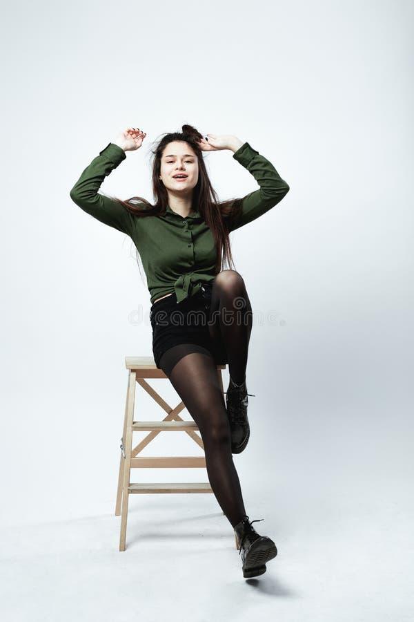 Młoda elegancka ciemnowłosa dziewczyna z śmieszną fryzurą ubierającą w zielonej koszula, czerń skrótach, rajstopy i butach, pozuj obraz stock