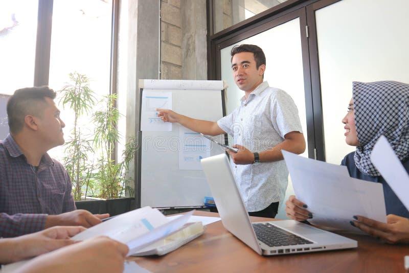 Młoda fachowa męska prezentacja przy spotkaniem grupowym w białej desce z pastylką i laptopem, biurowa spotkanie grupa blisko okn zdjęcia stock