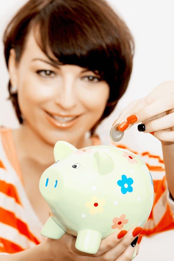 Młoda kobieta daje euro monecie w prosiątko banka fotografia royalty free