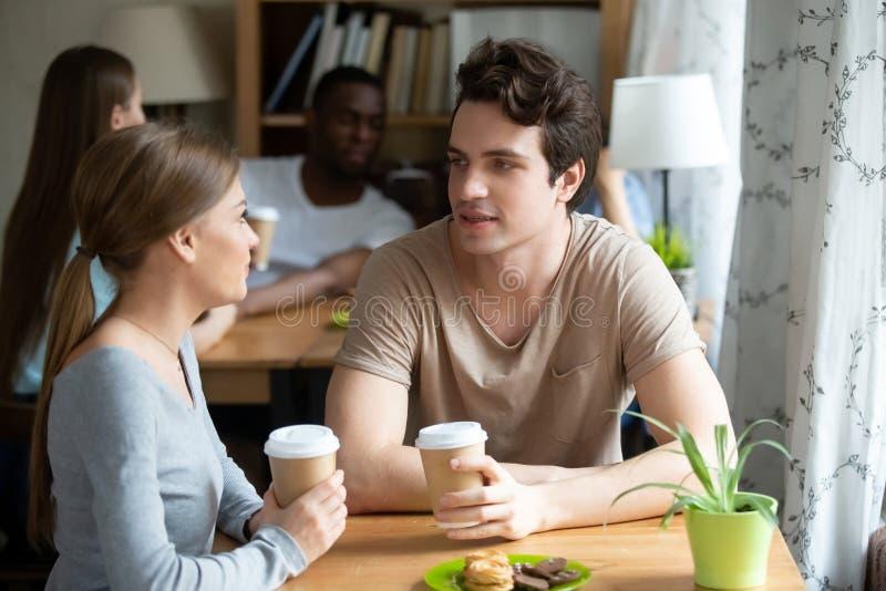 Młoda kobieta i mężczyzna cieszy się kawę i desery w kawiarni wpólnie fotografia stock