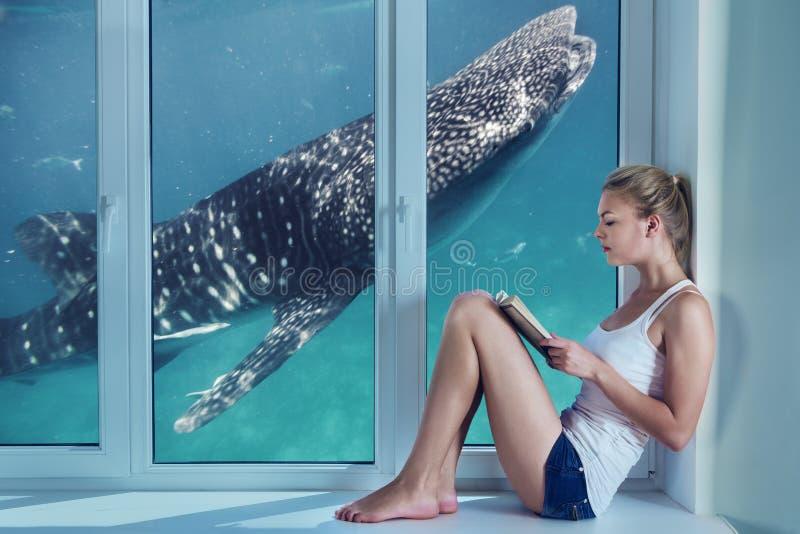 Młoda kobieta imaginating podwodnego życie podczas gdy czytający zdjęcia royalty free