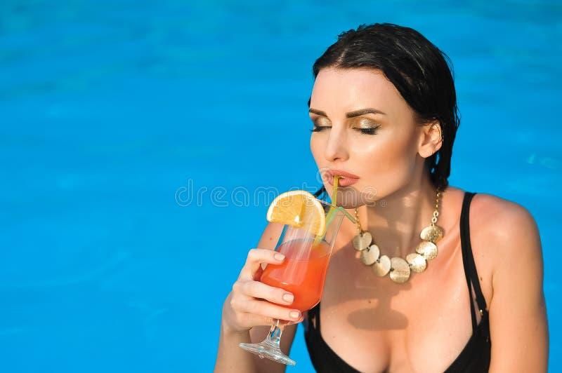 Młoda kobieta napoju alkoholu koktajl z pomarańcze na basenie obraz royalty free
