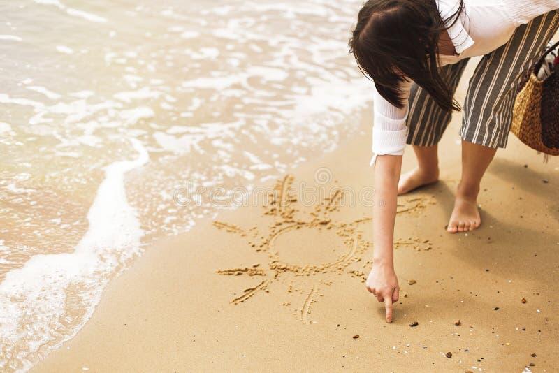 Młoda kobieta pisze słońcu na piasek plaży blisko morza i fal Modniś dziewczyna relaksuje na piaskowatej plaży i ma zabawę, odpro obrazy royalty free