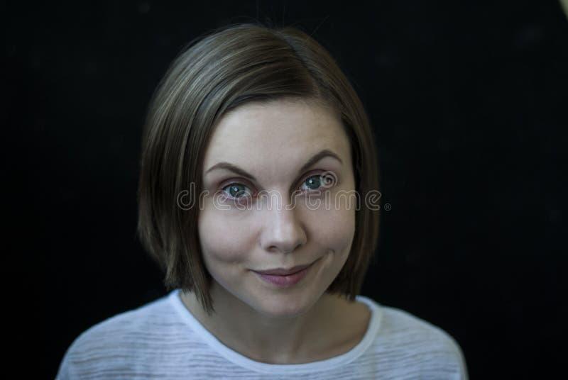 Młoda kobieta portret na czarnym tle, w górę, żywy wyraz twarzy zdjęcia stock