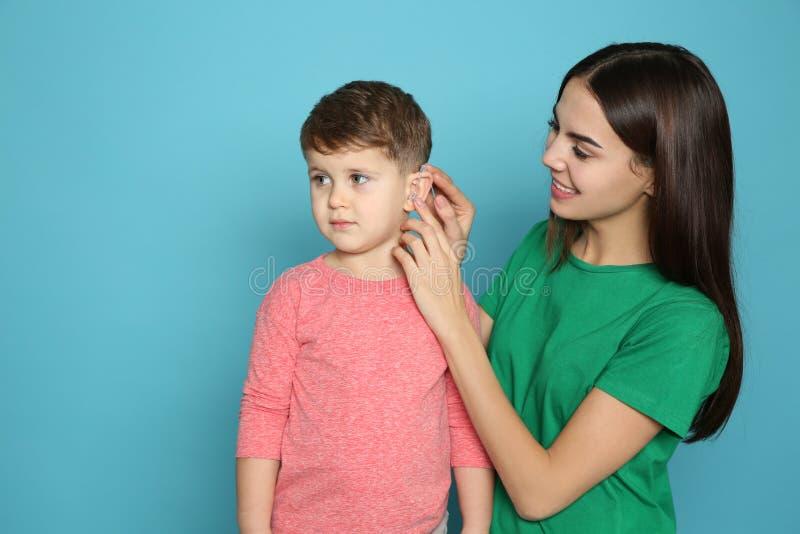 Młoda kobieta przystosowywa małą syna przesłuchania pomoc obrazy royalty free