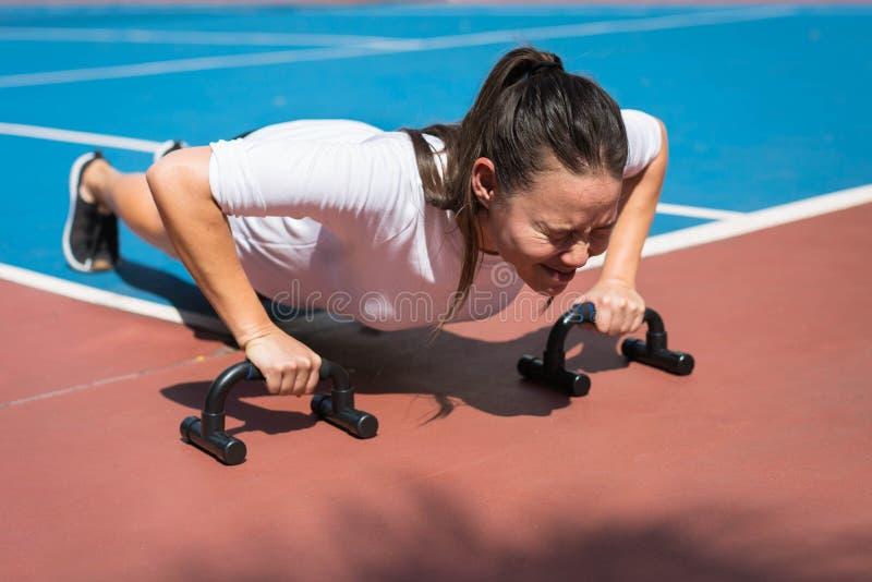 Młoda kobieta robi pushups outside, skołowany obraz stock