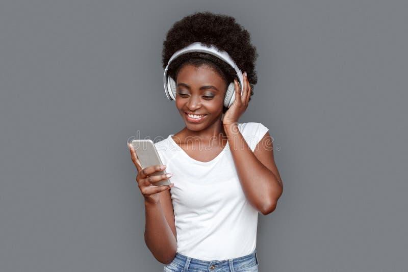 Młoda kobieta stoi odizolowywająca na szarej wybiera piosence na smartphone rozochoconym w hełmofonach zdjęcia stock