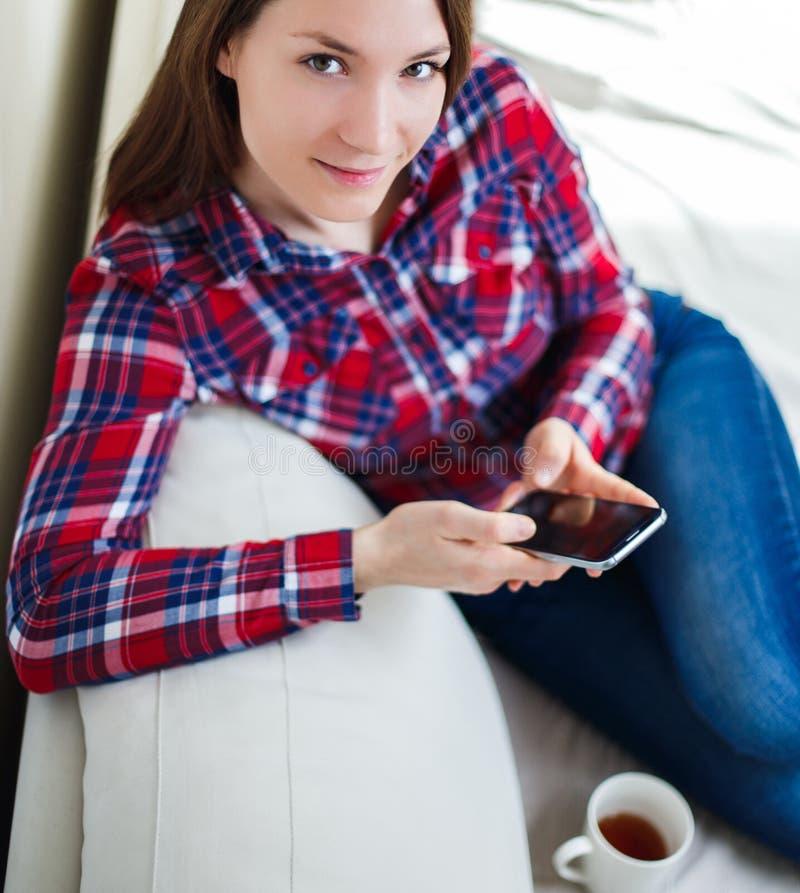 Młoda kobieta używa telefon komórkowego siedzi na kanapy relaksować w domu obraz royalty free