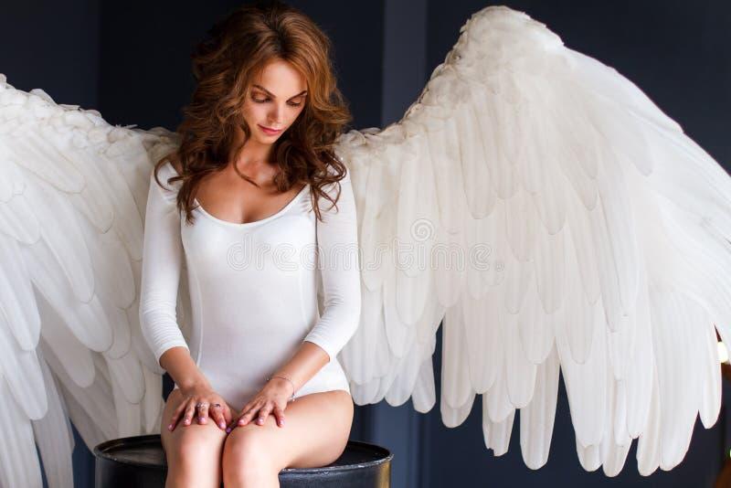 Młoda kobieta w białym bodysuit z aniołów skrzydłami zdjęcie stock