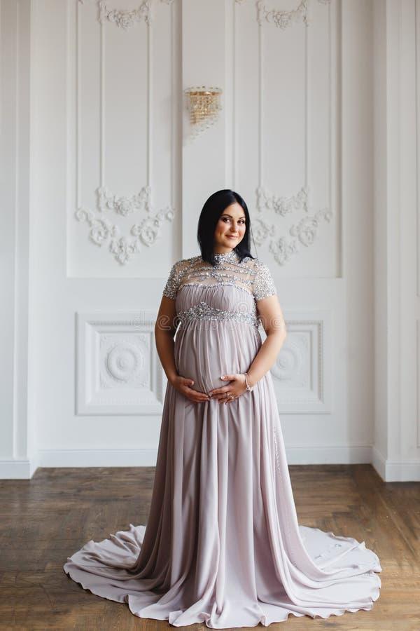 Młoda kobieta w ciąży w lekkim klasycznym wnętrzu fotografia royalty free