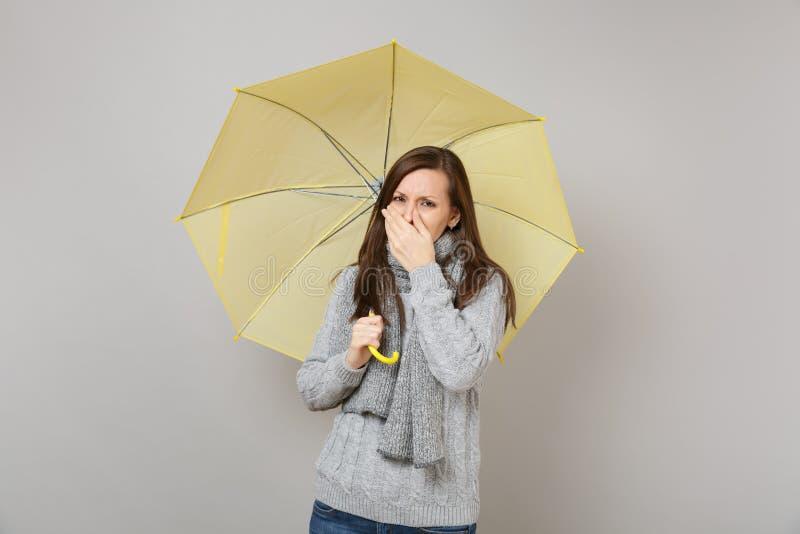 Młoda kobieta w szarym pulowerze, szalika nakrywkowy usta z ręką, kichnięcie lub kasłać, chwyta żółty parasol odizolowywający na  obraz stock