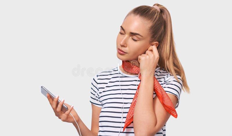 Młoda kobieta z ponytail, jest ubranym pasiastą koszulkę, elegancki czerwony szalik na szyi, relaksuje z zamkniętymi oczami słuch zdjęcia stock