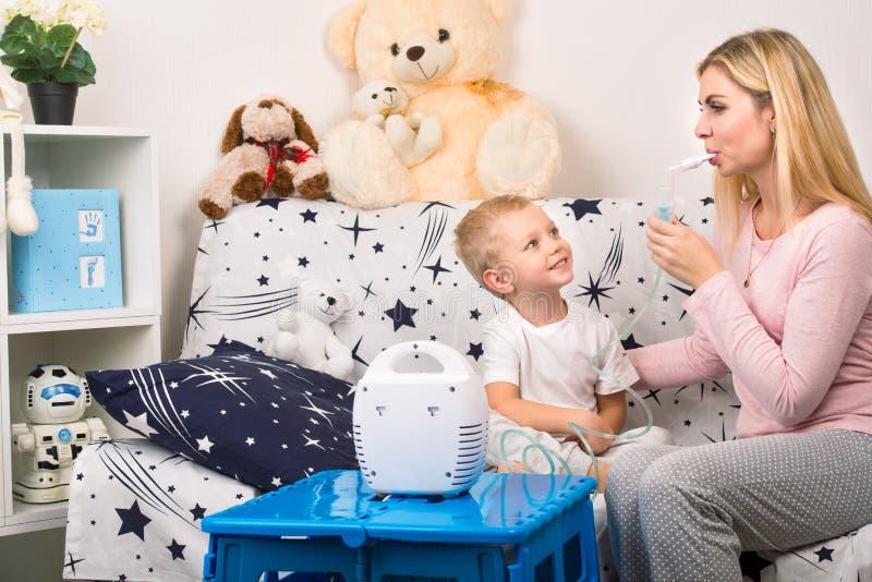 Młoda kobieta z synem robi inhalaci z nebulizer w domu Matka młode dziecko robi inhalaci obrazy royalty free