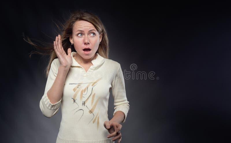 Młoda kobieta z włosiany trzepotać w zaskakującym spojrzeniu i wiatrze Krzyczy dziewczyna patrzeje w górę i gestykuluje z ona zdjęcia royalty free