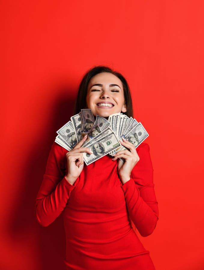Młoda myśląca ładna kobieta w czerwieni sukni prasach ona wiązka pieniędzy banknoty zdjęcie stock