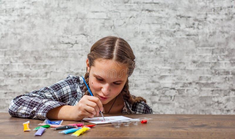 Młoda nastolatek brunetki dziewczyna z długie włosy rysunkiem z muśnięciem przy stołem na szarości ściany tle z kopii przestrzeni obrazy stock