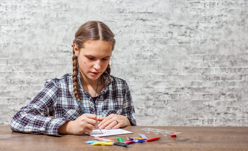 Młoda nastolatek brunetki dziewczyna z długie włosy rysunkiem z muśnięciem przy stołem na szarości ściany tle z kopii przestrzeni zdjęcie royalty free