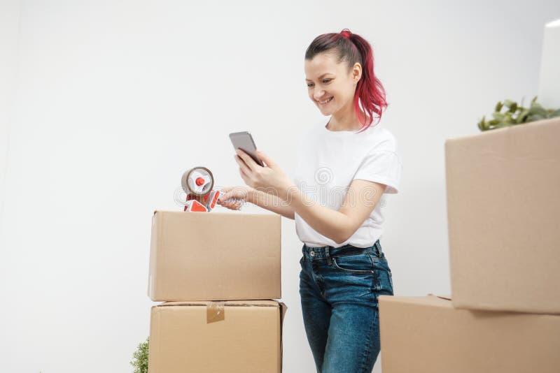 Młoda piękna brunetki dziewczyna w białej koszulce pakuje kartony z adhezyjny scotch adhezyjnym i aptekarką fotografia stock