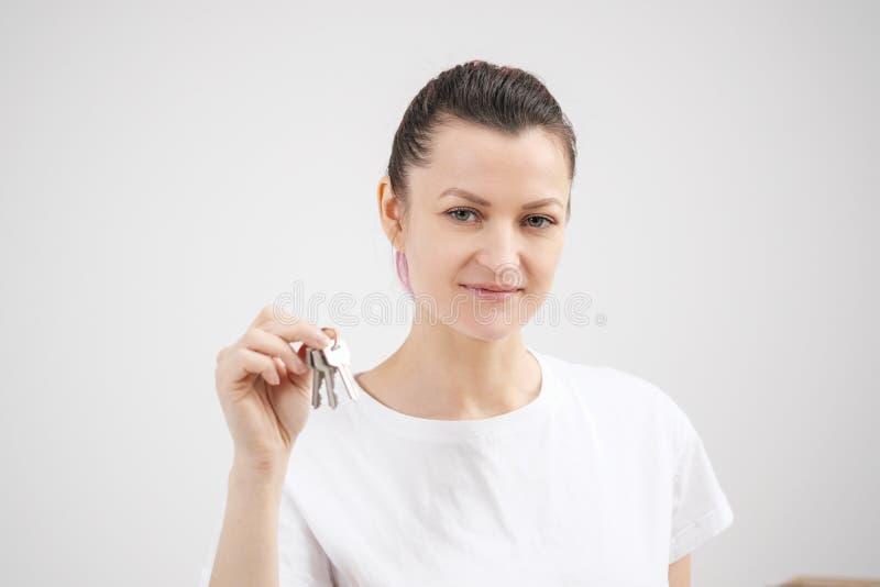 Młoda piękna brunetki dziewczyna w koszulki białych chwytach w jej rękach klucze nowy dom przeciw tłu, fotografia royalty free