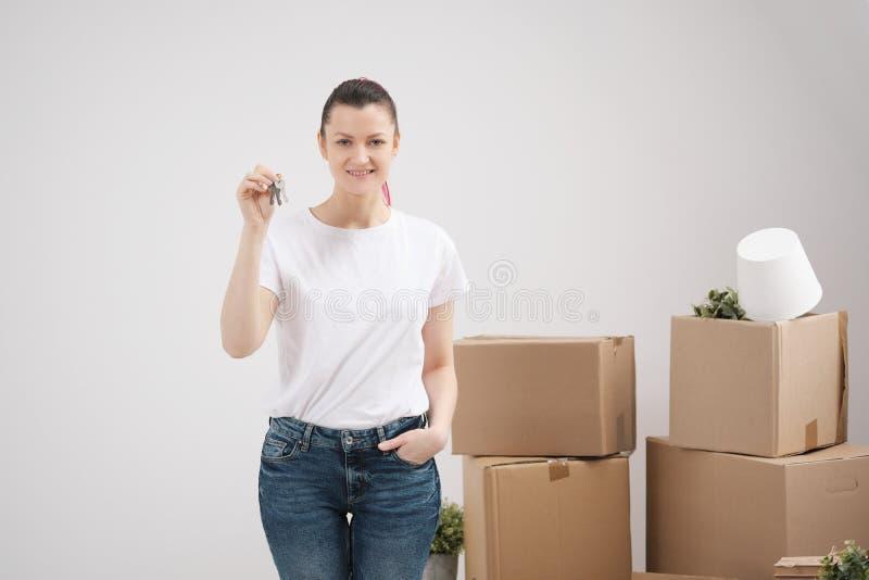 Młoda piękna brunetki dziewczyna w koszulki białych chwytach w jej rękach klucze nowy dom przeciw tłu, zdjęcie royalty free