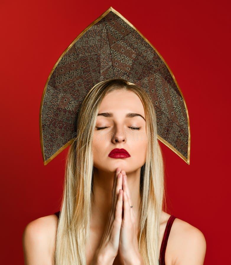 Młoda piękna caucasian kobieta wpólnie pyta dla coś o w kokoshnik nakrętki modleniu z rękami zdjęcia stock