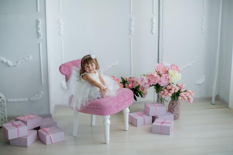 Młoda piękna dziewczyna trzyma bukiet balerina w białej menchii sukni stoi w białym pokoju blisko białego stołu zdjęcia stock
