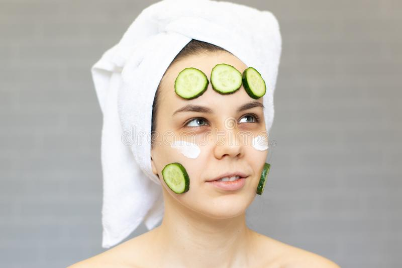 Młoda piękna dziewczyna z ogórków plasterkami na twarzy nad białym tłem Piękno kosmetologia i skincare zdjęcia royalty free